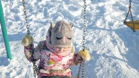 W zima parka dziewczynie na huśtawce