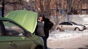W zimie, ciężarna dziewczyna jest przyglądająca dla pomocy od przelotnych samochodów w naprawie nieudany samochód zbiory
