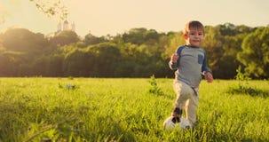 W zwolnionym tempie, szczęśliwa chłopiec marzy bawić się zawodową piłkę nożną z piłki nożnej piłką biega w pole przy zmierzchem zbiory