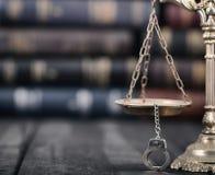 Waży sprawiedliwość i kajdanki na czarnym drewnianym tle Zdjęcie Stock