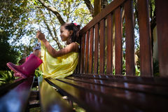 Waagerecht ausgerichtete Oberflächenansicht des lächelnden Mädchens, das Handy beim Sitzen auf Holzbank verwendet lizenzfreies stockfoto