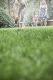 Waagerecht ausgerichteter Oberflächenschuß des Vaters springend durch eine Berieselungsanlage in der Gras-, Mutter- und Tochteruhr Lizenzfreies Stockfoto
