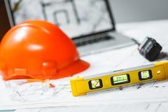 Waagerecht ausgerichtetes Meter mit unscharfem orange Schutzhelm, Laptop mit Zeichnungen und Funksprechger?t auf einem Hintergrun stockfotografie