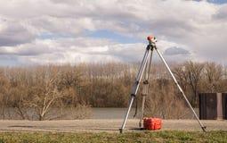 Waagerecht ausgerichtetes Werkzeug des Theodolits auf Hochwasserschutzverdammung stockbilder