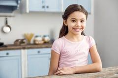 Waakzame meisjezitting in de keuken stock foto