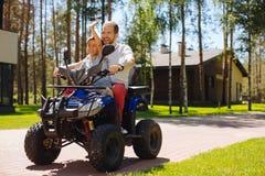 Waakzame mens en zijn zoonszitting op een ATV stock foto