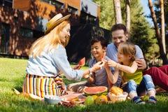 Waakzame moeder die een picknick met haar familie hebben royalty-vrije stock afbeeldingen