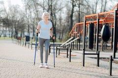 Waakzame vrouw die steunpilaren en het lopen gebruiken stock afbeeldingen