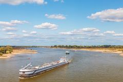 The Dutch Waal river near Nijmegen with cargo ships passing by Stock Photo