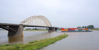 Waalbrug bridge, Nijmegen, the Netherlands. A container transport boat under Waalbrug bridge over the river Waal near Nijmegen, the Netherlands stock photography