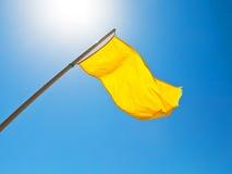 Waarschuwende gele vlag onder zon met blauwe hemel Stock Fotografie