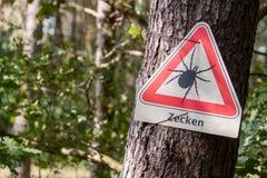 Waarschuwing vóór tikken in een Duits hout Stock Foto's