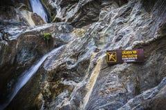 Waarschuwingsbord het gevaarlijke beklimmen bij waterval met stenen stock foto's