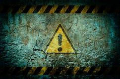 Waarschuwingssymbool op vuile muurachtergrond met grunge en vignet stock afbeelding