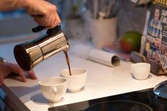 Wachen Sie auf und Kaffee von einem moka Topf gießen lizenzfreies stockbild