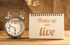 wachen Sie auf und leben Sie Text auf Notizbuch mit Wecker auf hölzerner Tabelle Stockfoto