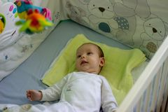 Wachen Sie babyboy im Feldbett auf stockfotografie