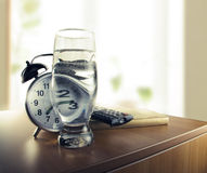 Wachen Sie mit der Alarmuhr und einem Glas Wasser auf Lizenzfreie Stockbilder