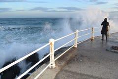 Waching de golven op een pijler Stock Afbeeldingen