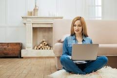 Wachsame Frau, die an einem Laptop sitzt auf dem Boden arbeitet Stockbild