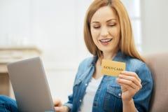 Wachsame Frau, die ihre Goldkarte betrachtet Stockfoto