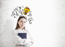 Wachsame Frau mit einem Buch, einer Birne und Fragen Stockbild