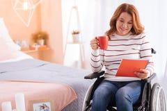 Wachsame lächelnde behinderte Frau, die eine Schale und ein Notizbuch hält Stockfotos