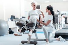 Wachsamer alter Mann auf einem Trainingsgerät und seinem Trainer stockfotos