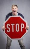 Wachsamer Mann, der Stoppschild zeigt. Stockbilder
