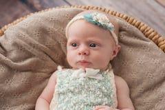 Wachsames Baby, das in einem Weidenkorb liegt Stockbilder