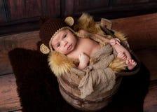 Wachsames neugeborenes Baby, das einen Affe-Hut trägt Lizenzfreie Stockfotos
