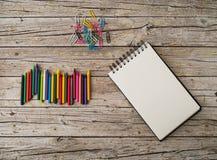 Wachsen Sie Bleistifte, Büroklammern und Notizbuch auf hölzernem Hintergrund ein Stockfotografie
