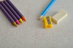 Wachszeichenstifte, ein Schreibensbleistift, Bleistiftspitzer und Radiergummi Lizenzfreies Stockbild