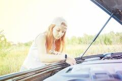 Wacht op kant van de weghulp Portret van een jonge vrouw die zich naast haar auto bevinden die de motor proberen te bevestigen royalty-vrije stock foto's