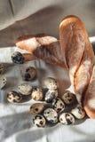 Wachteleier und frisches Weißbrot, ein Laib auf der Tischdecke Stockfoto