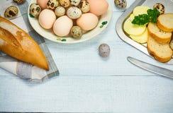 Wachteleier und Hühnerei mit Brot und Butter Lizenzfreie Stockbilder