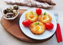 Wachteleitoast, Ei in einem Korb mit Wachteleiern, Safran, Kirschtomaten Stockbilder