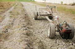 Wachten de schade oude Tractor en het Aanhangwagen slepende einde op Padiegebied s Stock Afbeeldingen