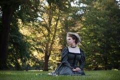 Wachtende damezitting in het gras Stock Afbeeldingen