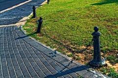 Wachtpolen aan kettingen tussen gras en een stoep worden verbonden die stock foto's