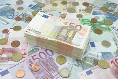 Wad of fifty euros bills. Wad of fifty euro on a background full of money stock images