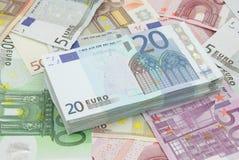 Wad of twenty euros bills. Wad of twenty dollars on a background full of money stock photo