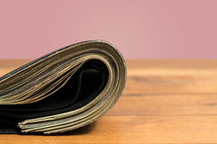 Wad of US dollar bills in black wallet on table Stock Image