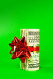 A wad of US one hundred dollar bills. Tied up with red ribbon over green background Royalty Free Stock Images