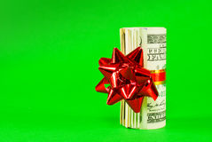 A wad of US one hundred dollar bills. Tied up with red ribbon over green background Stock Photography