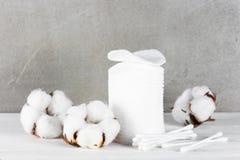 Wadded垫、棍子和棉花花在木桌上 免版税库存图片
