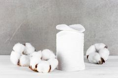 Wadded pads and cotton flowers on the table. Wadded pads and cotton flowers on the wooden table against the gray wall Royalty Free Stock Photos
