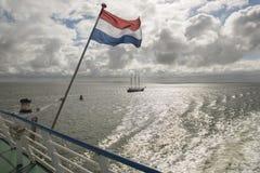 Wadden hav med den holländska flaggan som sett från färjan Arkivfoto