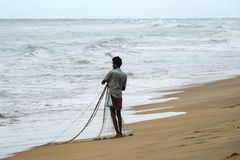 Wadduwa Sri Lanka - Maj 08, 2018: En fiskare med fisknät på stranden i Sri Lanka arkivbild