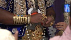 Wadduwa Sri Lanka - Maj 11, 2018: Härlig gifta sig ceremoni i Sri Lanka Nygifta personer i traditionella dräkter står under bågen lager videofilmer
